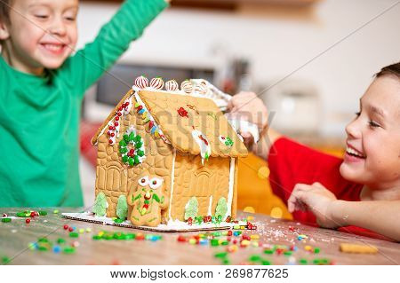 Children Having Fun Decorating The Gingerbread House. The Concept Of Family Preparing To Christmas.