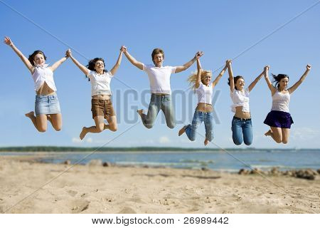 The image of a group of friends that are jumping on the beach
