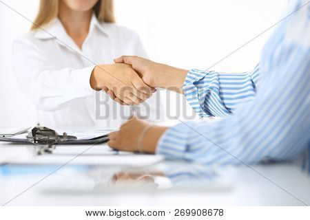 Business Handshake At Meeting Or Negotiation In Office. Partners Shaking Hands While Satisfied Becau