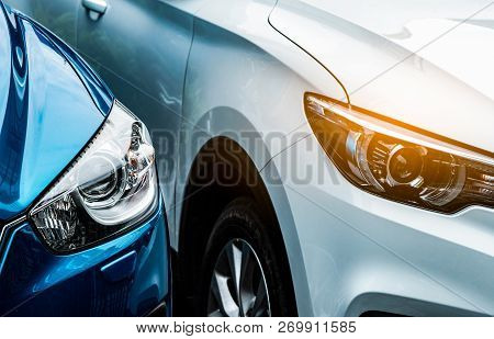 Close Up Headlamp Light Of Blue And White Suv Car. Blue Car Parked Beside White Car. Automotive Indu