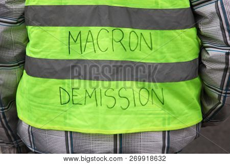 Villefranche en Beaujolais, France - November 19, 2018: Yellow vests protest against higher fuel prices in France and text on the yellow vest president Macron departure in French