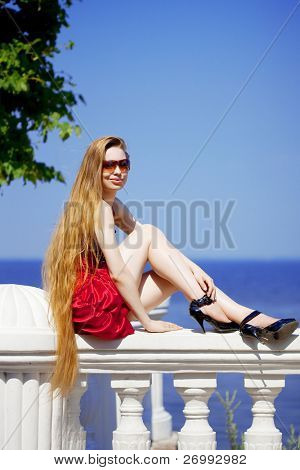 The image of a beautiful girl in the red dress on the beach