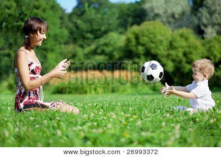Kép a család, az anya és a fia labdáztak a parkban.