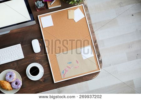Workplace of business person with noticeboard, cup of black coffee, pastry, document and computer