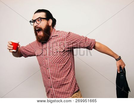Young Bearded Man Running Wearing Glasses, Is Late To Work, Coffee To Go. Young Man Scared To Be Lat