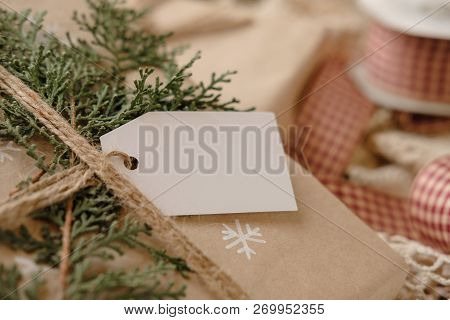 Blank Gift tag on Classy vintage Christmas gift box. Christmas presents with handmade decoration. Close up. Mockup. Copy space. poster