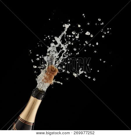 Explosion of splashing  sparkling wine with flying cork out of champagne bottle on a black background