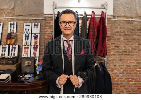 Senior male tailor choosing fabric at his atelier. poster