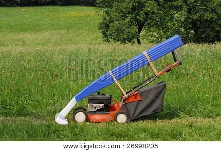 Orange lawn mower and big razor resting in backyard.