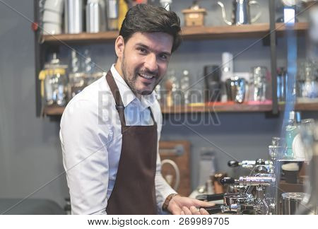 Portrait Of Bearded Barista In Apron Smiling At Camera And Preparing Coffee At Counter. Small Busine