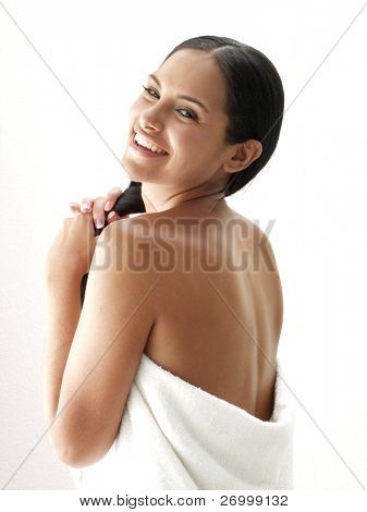 Beautiful young latin woman on white background. Closeup portrait of young beautiful woman and towel after bath - spa.