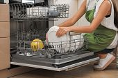 Young woman loading dishwasher in kitchen, closeup. Cleaning chores poster