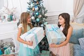 Kids little sisters hold gifts boxes interior background. Children friends excited unpacking their gifts. What a great surprise. Small cute girls received holiday gifts. Best toys and christmas gifts. poster