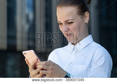 Young Angry Frowning Disgusted Business Woman Surfing Smartphone In Dislike, Talking, Typing On Mobi