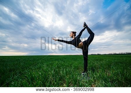 Beautiful Girl Gymnast On The Green Grass Do Yoga. A Beautiful Young Woman On A Green Lawn Performs