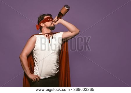 Super Antihero Man Drinks Alcohol From The Throat Of A Bottle. Isolated On Grape Purple Background W