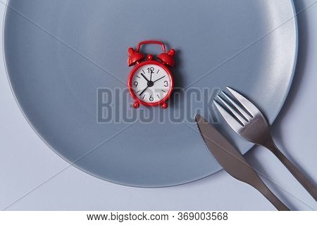 Time To Eat Background. Top View Of Red Alarm-clock In Empty Table With Knife And Fork. Isolated On
