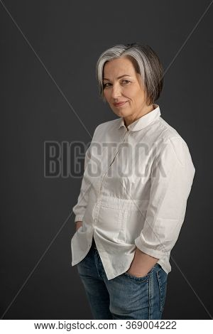 Gray-haired Mature Woman Smiles Holding Hands In Pockets While Looking At Camera. Charming Caucasian