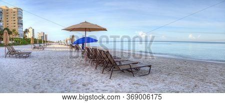 Umbrellas And Chairs On Vanderbilt Beach At Sunrise With A Calm Ocean And Buildings Along The White