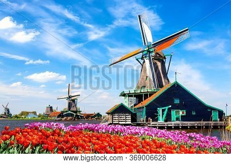 Typical Iconic Landscape In The Netherlands, Europe. Traditional Old Dutch Windmills With House, Blu