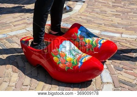 Keukenhof Lisse, The Netherlands - May, 2018: Man Standing In Big Red Wooden Clogs Shoes In A Dutch