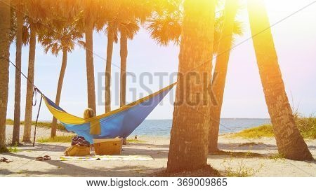 Romantic Couple Relaxing On Tropical Hammock. Young Couple In Love Relaxing In A Hammock By The Beac