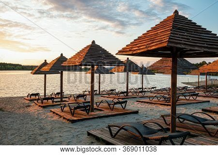 Empty Rows Resting Places On Evening Sandy Beach With Brown Wooden Loungers And Umbrellas. Empty San