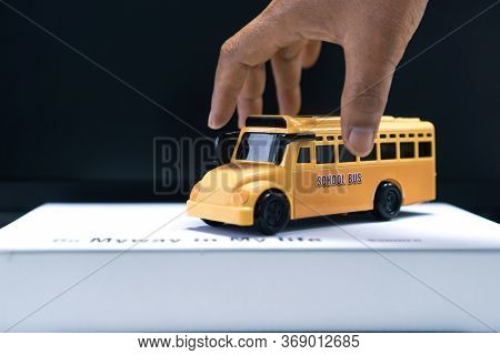 Hands Holding School Bus For Student Transport For Children Transports Service On Stack Books With W
