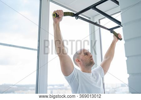 Man Goes In For Sports Doing Pull-up Exercises On Horizontal Bar At His Home