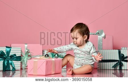 Cute Little Baby Girl Surrounded By Heaps Of Gifts In Pink Boxes With Bows. On A Pink Pastel Backgro