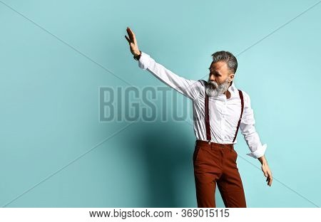Gray-haired Man In Years In White Shirt, Brown Pants And Suspenders, Black Loafers. He Runs Looking