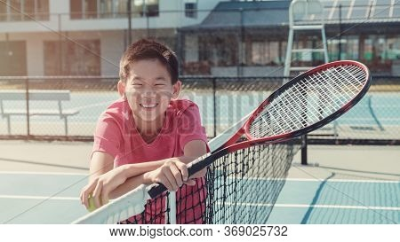 Young Healthy And Happy Tween Preteen Mixed Asian Boy Tennis Beginner Player On Outdoor Blue Court,