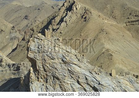 Ruined Towers Of A Stone Building Remain On The Edge Of A Cliff In Ladakh, India. Another Tower Lowe