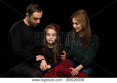 Portrait Of Loving Parents Hugging Their Adorable Daughter, Mom And Dad Sitting On The Floor And Loo