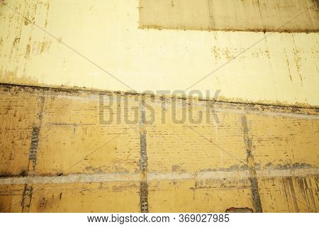 Brick Wall Of An Old House Painted Yellow And Ocher Colors. Weathered Stained Wall Textured Backgrou