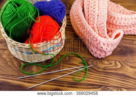 Wicker Basket With Colorful Knitting Yarns, Knitting Needles And Knitted Scarf On Wooden Table