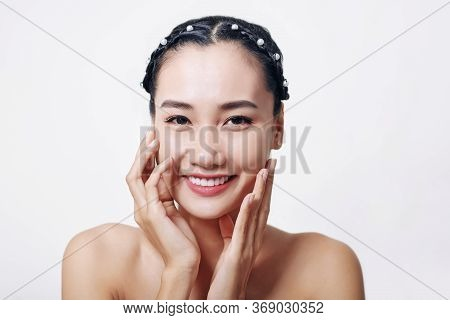 Portrait Of Attractive Young Asian Woman Touching Her Flawless Tender Skin And Lookng At Camera
