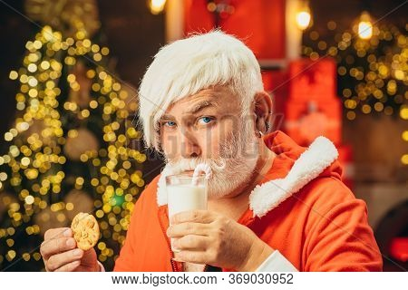 Santa Claus Takes A Cookie On Christmas Eve As A Thank You Gift For Leaving Presents. Santa Claus In