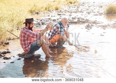 Portrait Of Cheerful Senior Man Fishing. Happy Bearded Fisher In Water. Fishing As Holiday. Fishers