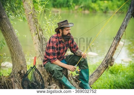 Man Fishing On River. Sitting Alone During The Fishing Process On The Pier Near The Lake. Mature Man