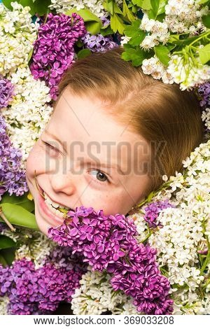 Funny Facial Portrait Of Beautiful Little Girl Winking. Teenager Girl With Bouquet Of Purple And Whi