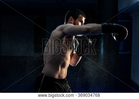 Young Male Boxer Hitting Punching Bag On Black Background