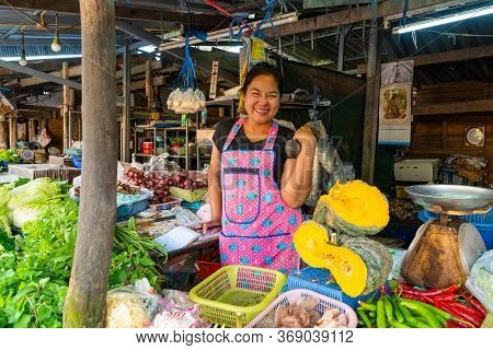 Beautiful Asian Girl Vegetable Seller At The Market Lifts A Dumbbell To Keep Fit. Samui / Tailand -
