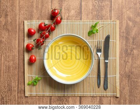 Empty Yellow Plate With Tomato And Basil Decoration. Conceptual Shot Of A Typical Italian Lunch And