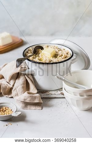 Old Fashioned Rolled Oat Porridge With Melting Butter In A Sauce Pan And Chopped Almond Nuts, Copy S