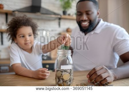Cute Curly-haired Kid Putting Coins Into The Moneybank