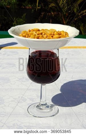 Glass Of Red Wine With Dish Of Peanuts On Top To Keep Flies Off (modern Tapas Originates From The Th
