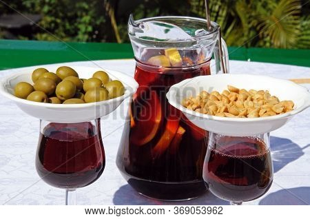 Jug And Glasses Of Freshly Made Spanish Sangria With Nibbles/tapas On Top Of The Glasses To Keep Fli