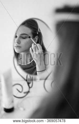 Black-white. Beautiful Girl Doing Make-up And Looks In The Mirror. Care Of Yourself.