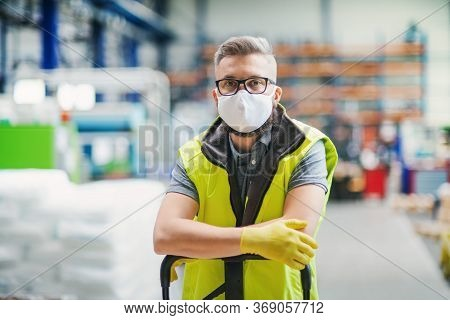 Man Worker With Protective Mask Standing In Industrial Factory Or Warehouse.